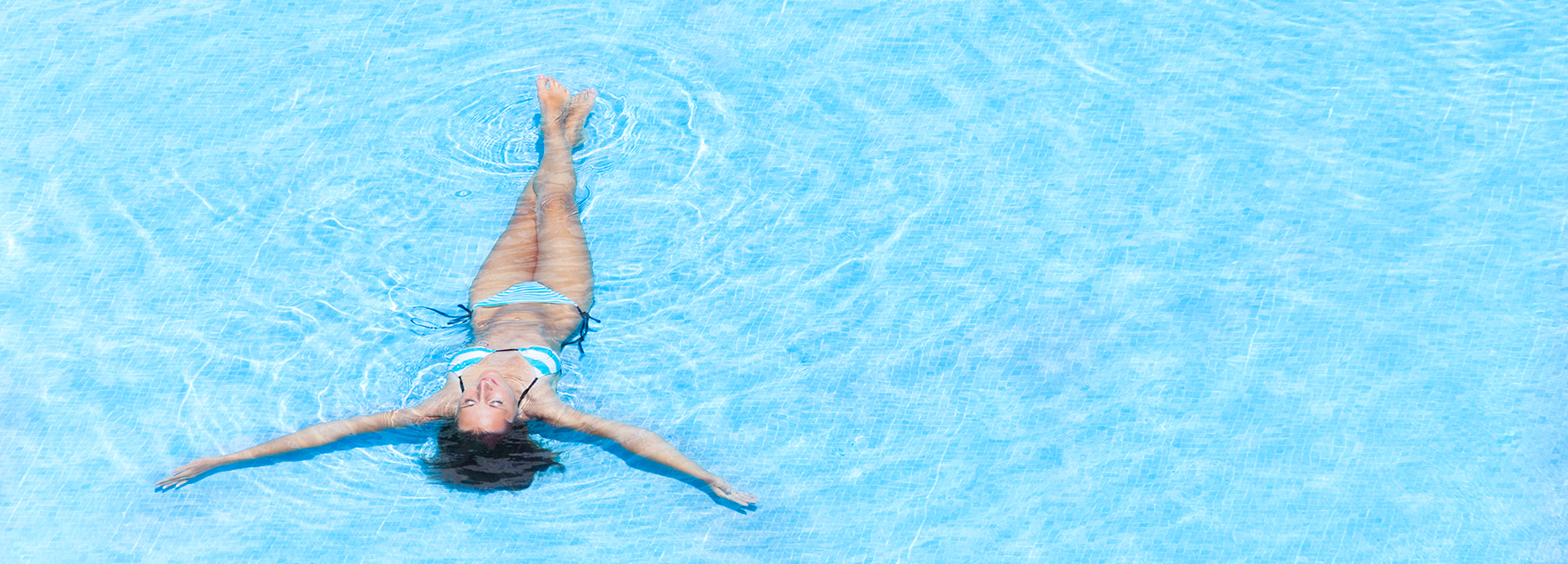 Young woman swimming in the crystal-clear pool
